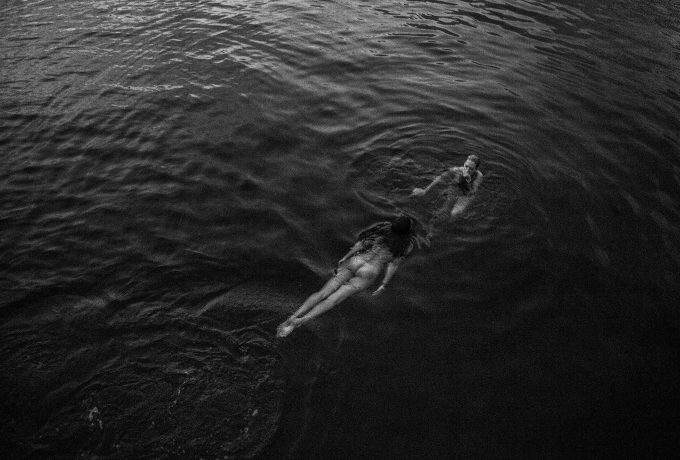 Two women swimming in the middle of the ocean.